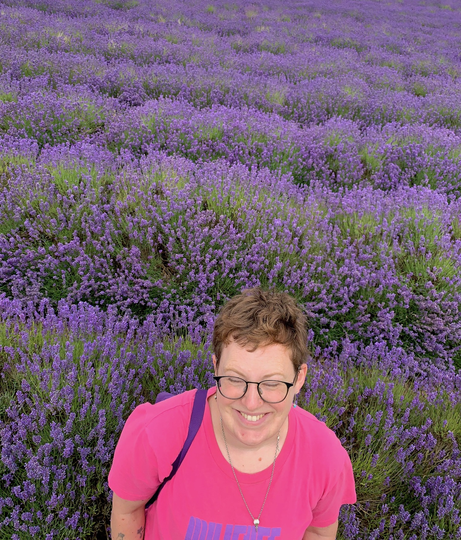 person with short hair and pink shirt standing in lavender field